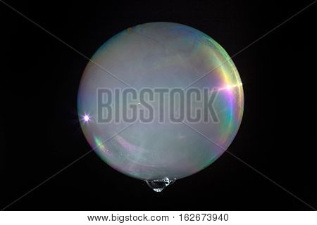 Floating Soap Bubble Filled With Smoke Isolated On A Black Background