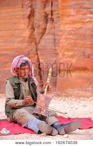 PETRA, JORDAN - MARCH 11, 2016: A Bedouin musician playing and singing in the Outer Siq