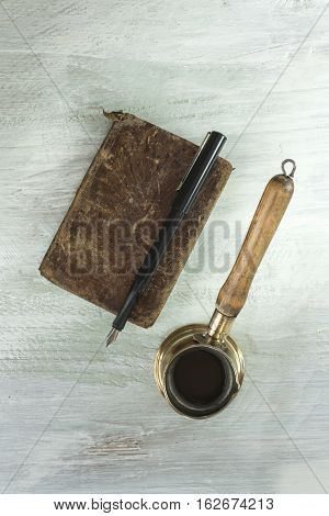 A photo of a vintage coffee pot with a wooden handle, shot from above on a light wooden background texture with copyspace, next to an old book with an ink pen