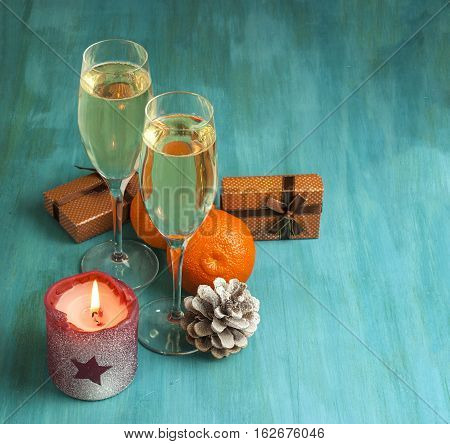Photo for Christmas or New Year card. Burning candle with star shape on it, pine cone with tangerines, champagne, and little present boxes in the background. Selective focus and copyspace