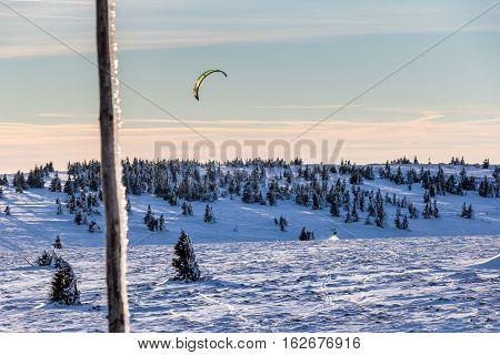 Snowkiter with kite on snowy field under blue sky