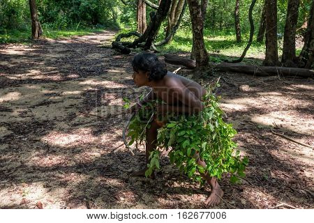 DABANA, SRI LANKA - CIRCA DECEMBER 2016: Vedda man holding bow and arrows during hunting. Veddas are an indigenous people of Sri Lanka living in tribes in the jungle