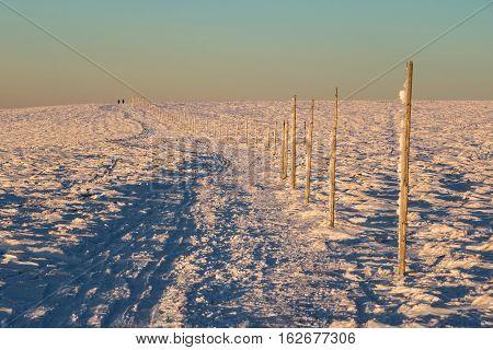 Silhouette Of Tourists On Marked Path Along Mountain Ridge