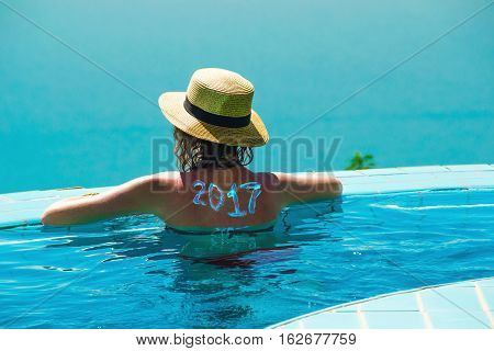 Photo of the Woman from behind in hat and infinity pool looking away. New travel season concept. 2017 written on back by suncream