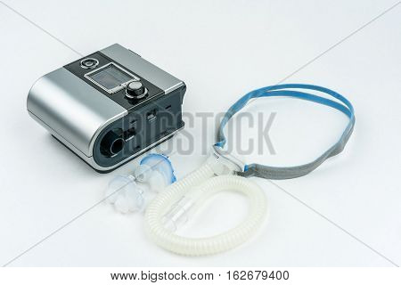 CPAP machine with hose and mask for nose. Treatment for people with sleep apnea, respiratory, or breathing disorder.
