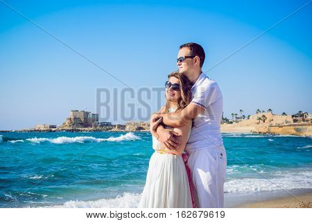 Happy Romantic Couple On The Sea Beach Embracing Each Other. Man And Woman In Love Looking Ahead To