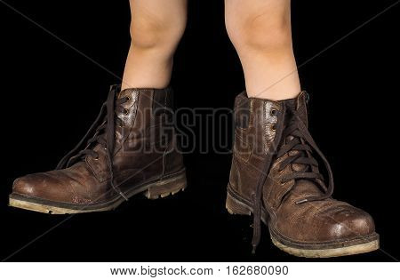Kid wearing a pair of too big untied and unpolished brown leather boots on black