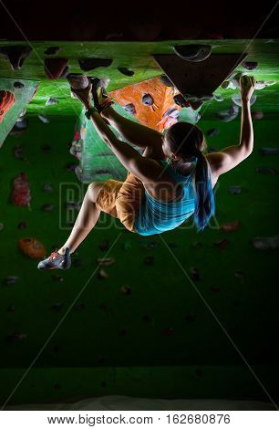 Young woman bouldering on ceiling of indoor climbing gym