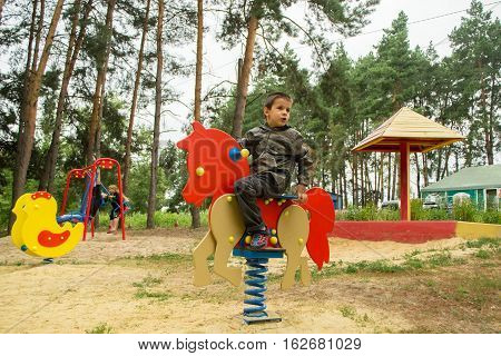 Happy baby child riding an orange horse at the playground