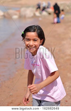 AQABA, JORDAN - MARCH 15, 2016: Portrait of a cute little girl laughing on a beach