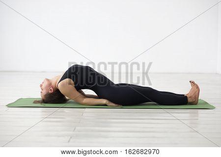 girl doing yoga asana Matyasana - fish pose.