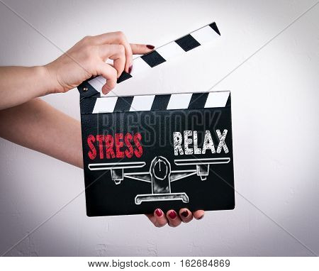 Stress and Relax Balance. Female hands holding movie clapper.
