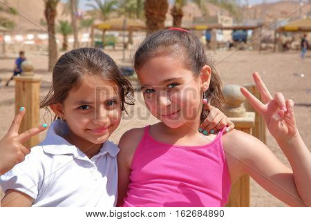 AQABA, JORDAN - MARCH 15, 2016: Portrait of two cute little girls smiling on a beach