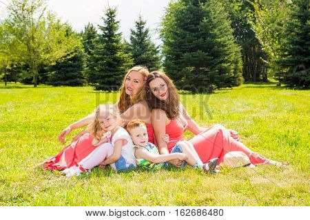 Happy family. Young mothers and kids boy and girl on sunny day. Portrait moms and children on nature. Positive human emotions feelings joy.