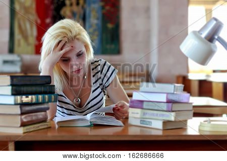 Tired blond, student or schoolgirl, looking thoughtfully into the book while sitting at a desk