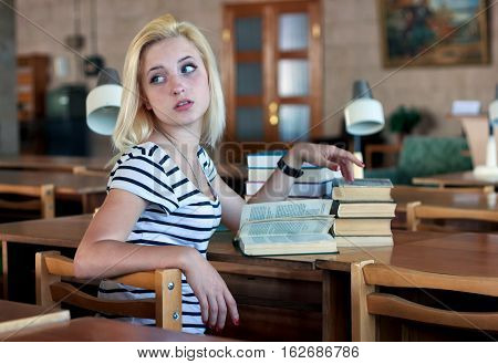 Tired girl coquettishly turns around to look back. She sits at a table on which there are a pile of books and reading lamps