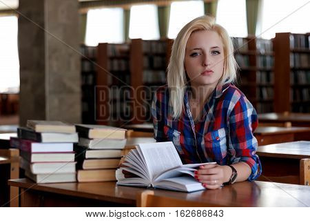 Young blonde woman sitting at the table. In the background are the rows of bookshelves. She holds in her hands an open book. Her haughty gaze directed at the camera