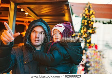 Happy family spend time at a Christmas and New Year holidays in the old town of Klagenfurt Austria. Holidays Christmas Family concept. Father and son at winter outdoor among Christmas decorations