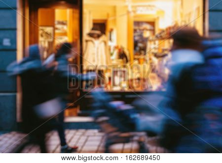 Defocused image of people walking in front of windows of shopping sotres during Christmas Maket to buy presents and toys