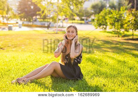 Headphones concept. Beautiful girl relaxing and listen music in the headphones in the city park on background. Woman in the headphone