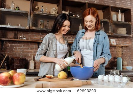 Help me. Red haired woman wearing casual clothes standing near the table mixing pastry while her friend is pouring milk