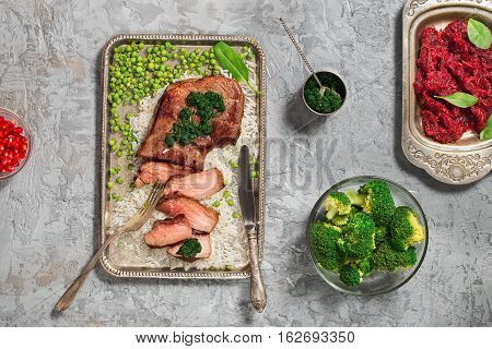 Sliced grilled beef with peases on the metal tray and red salad near top view
