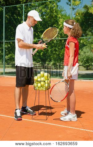 Tennis coach instructing young player, toned image