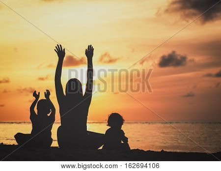 happy mother with two kids having fun on sunset beach