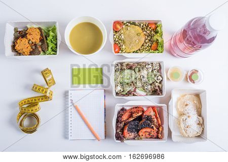 Healthy nutrition plan. Fresh daily meals delivery. Restaurant food for one vegetable meat and fruits in foil boxes detox water a measuring tape business card notebook and pencil on white background.