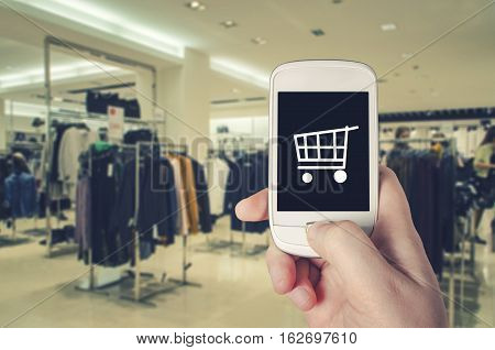 Hand holding smart phone with shopping cart icon on screen with blurred background of retail clothing store