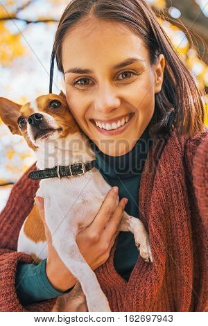 Smiling Young Woman With Dog Outdoors In Autumn Maki