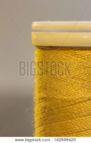 Spool of color threads in yellow. Close up