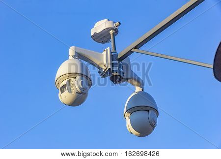 Security cctv cameras on pylon in blue background