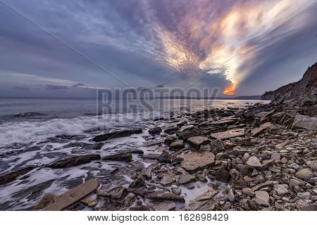 Exciting autumn sunset.Beauty sea rocky coast and cleavage sky