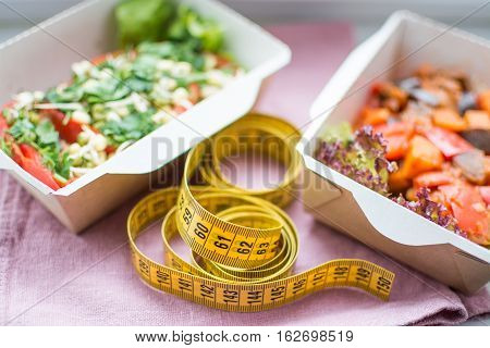 Healthy nutrition plan. Fresh daily meals delivery. food for weight loss in boxes and a measuring tape