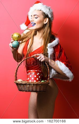pretty cute sexy santa girl or smiling blonde woman with fashion blue lips in new year swimsuit and hat holds decorative christmas or xmas basket with colorful balls on red studio background