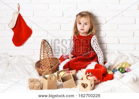 young cute little blonde girl in christmas red dress sitting around xmas basket or new year boxes gifts and colorful balls with decorative stocking or boot on white brick wall background