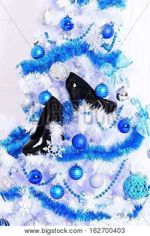 white fluffy christmas tree decorated with colorful blue balls with silver snowflakes new year decorative beads and garlands or festoon with black patent leather shoes on white studio background poster