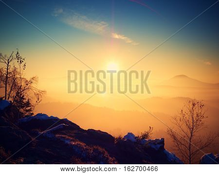 Marvelous Daybreak Above Valley Full Of Colorful Mist. Peaks Of High Trees