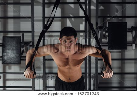 Handsome young muscled man training while working out in gym
