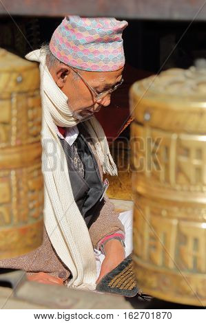 PATAN, NEPAL - DECEMBER 19, 2014: A Nepalese man reading Bhudist prayers at the Golden Temple with prayer wheels in the foreground