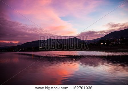 Sunset with pink clouds reflected in a lagoon in Cumbayá