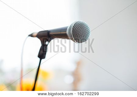 Vocal Microphone In Focus Against Blurred Audience At The Conference
