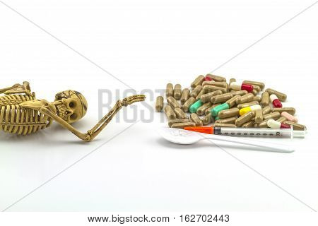 Skull and drugs with insulin syringe. Next to them are a spoon with white powder which is similar to heroin on white backgroundtouch - up in still life concept.