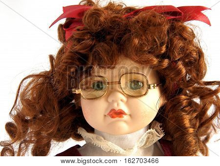 Closeup face of vintage porcelain doll with spectacles on white