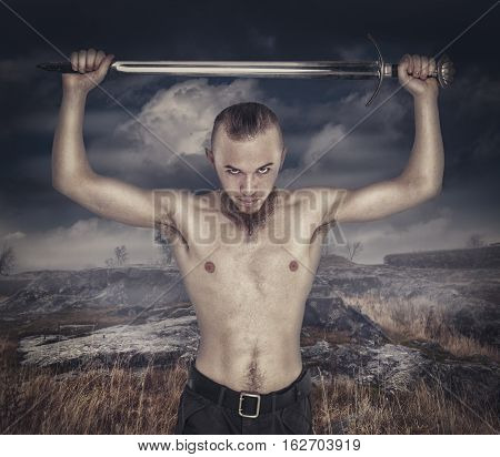Young Brutal Man With Sword Over Cloudy Background