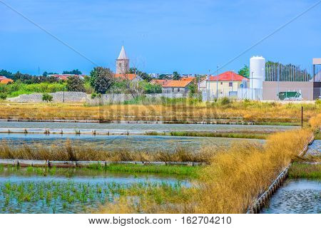 View at scenic in old croatian place with salty fields in foreground, european travel destination.