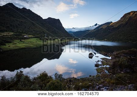 Papallacta lagoon at sunset with clouds and mountain