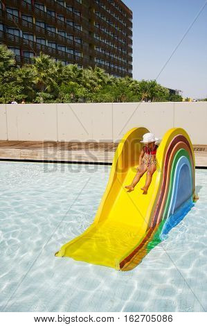 Little funny girl pretending sad sitting on a colorful mini waterslide in bright pool.