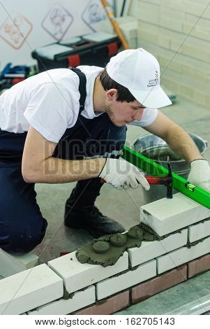 Tyumen, Russia - March 23. 2016: Open championship of professional skill among youth. World skills Russia Tyumen - 2016. Bricklayer performs a task of competition of professionals